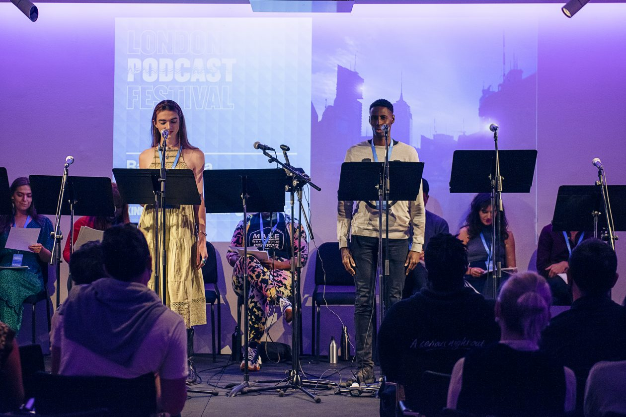 Mary Malone and Joseph Adelakun on stage performing at the London Podcast Festival for Radio Elusia Live. Stood in front of the Radio Elusia artwork depicting a skyline of high rise tower blocks.