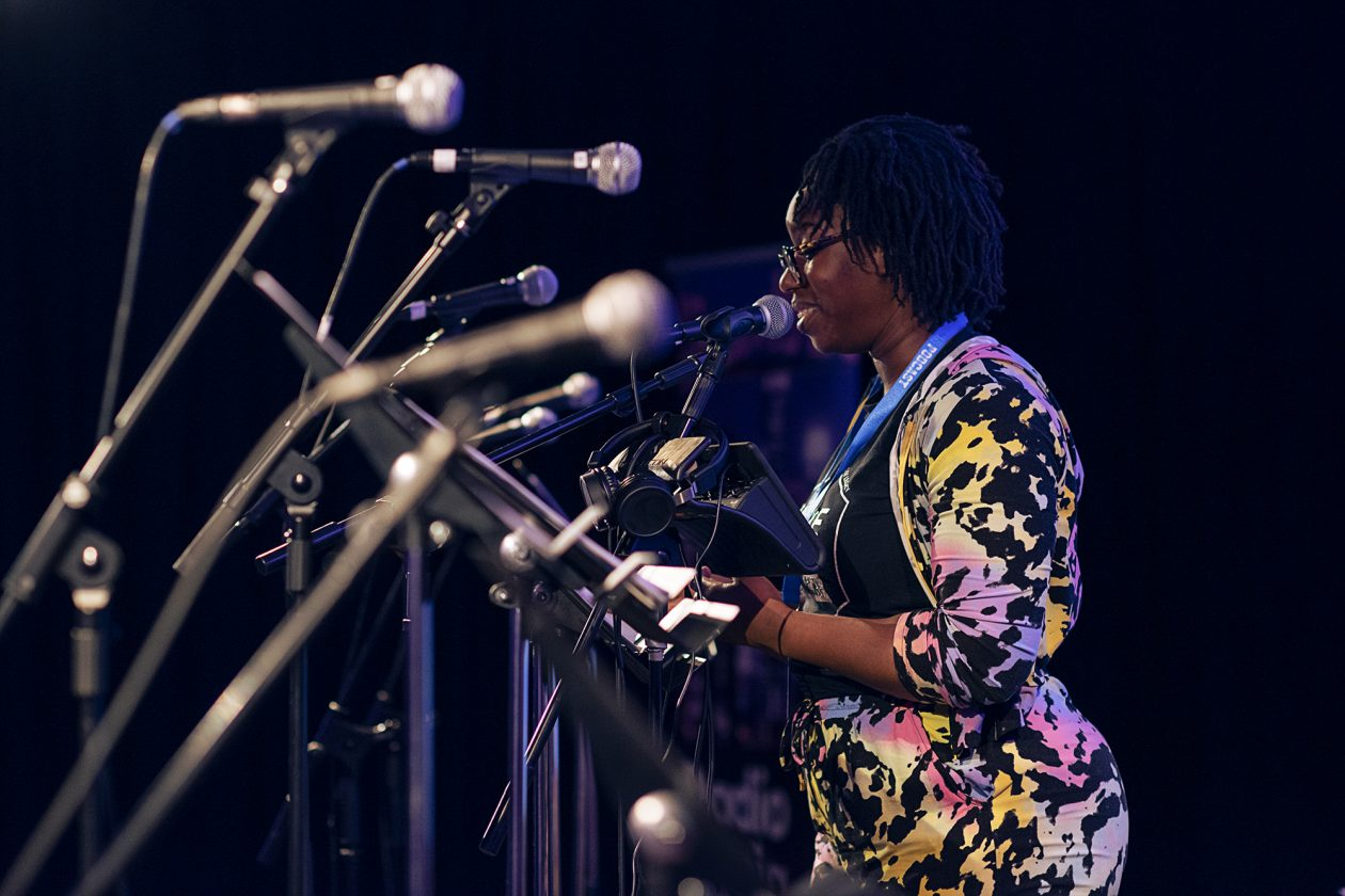 Aminita Francis performing as Lenses at the London Podcast Festival for Radio Elusia Live. Aminita is wearing a pink, yellow, black and white camouflage like outfit and is stood behind a row of microphones.