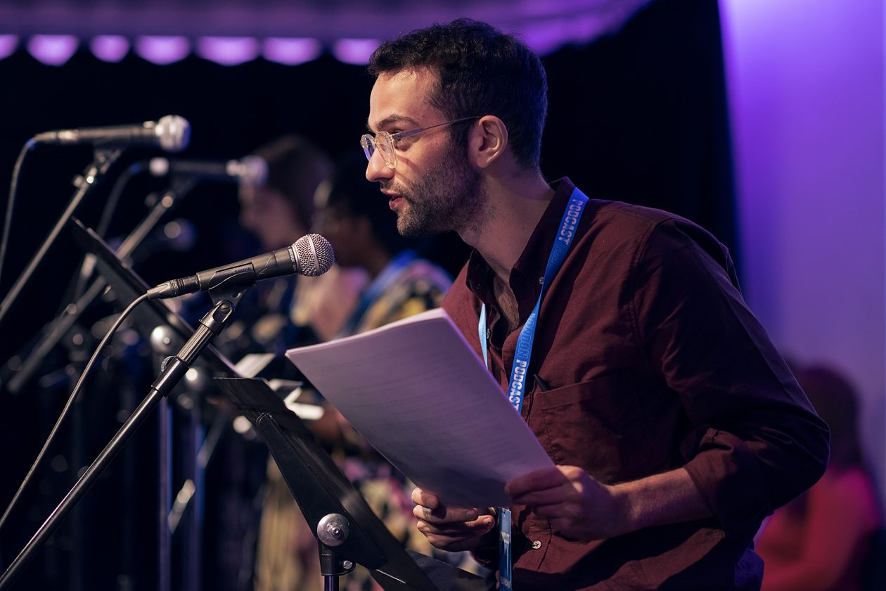 Pip Williams performing at the London Podcast Festival for Radio Elusia Live. Pip leans in to the microphone with his script in his hand, wearing a dark red button down shirt.