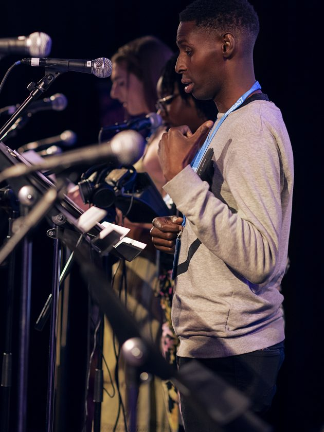 Joseph Adelakun performing at the London Podcast Festival for Radio Elusia Live. Joseph standing on stage behind a row of microphones, wearing a great sweatshirt and pointing over his right shoulder.