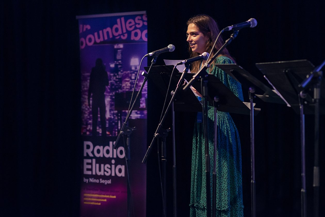 Megan Jarvie performing at the London Podcast Festival as part of Radio Elusia Live. Megan stands behind a microphone and is wearing a green dress, and is stood next to a pop up banner from Boundless Theatre for Radio Elusia.